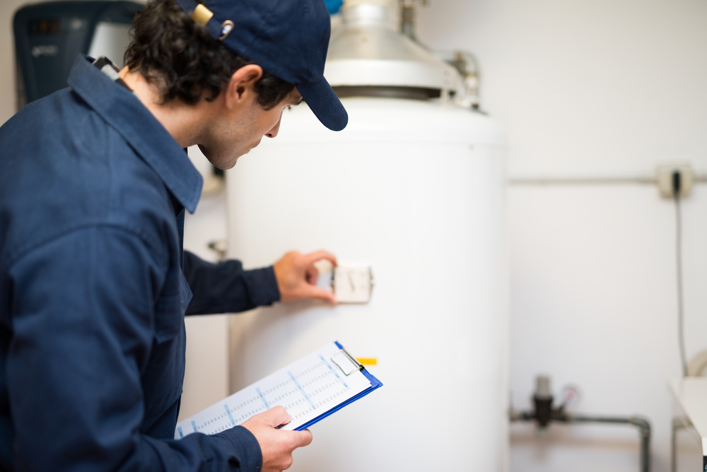 A plumber looks at a water heater gauge.