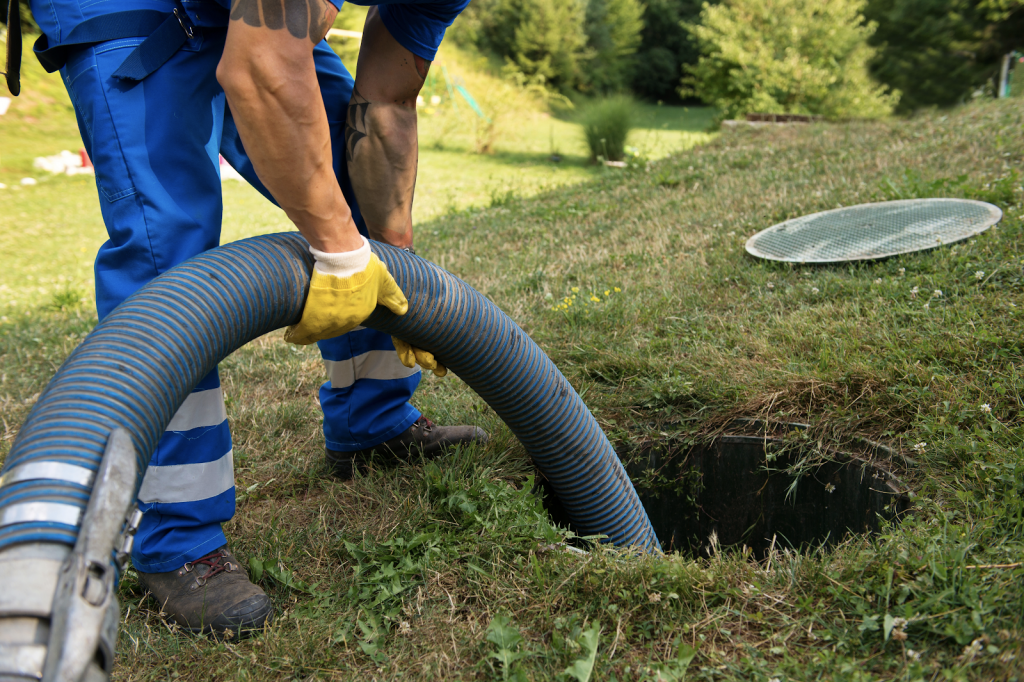 Repairman servicing a septic system. Reichelt Plumbing.