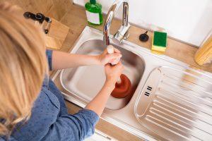 Woman using plunger to clear kitchen sink. Reichelt Plumbing, Schererville, IN.